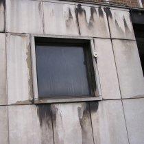 Wykruszone i spękane płyty betonowe budynku biurowego