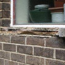 Uszkodzone parapety okien pod wpływem korozji belek wzmacniających