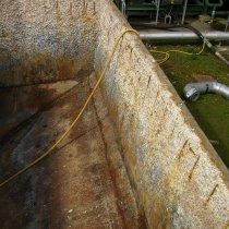 Znaczne uszkodzenia korozyjne belek wzmacniających oraz betonu w zbiorniku ścieków pod wpływem oddziaływania substancji chemicznych